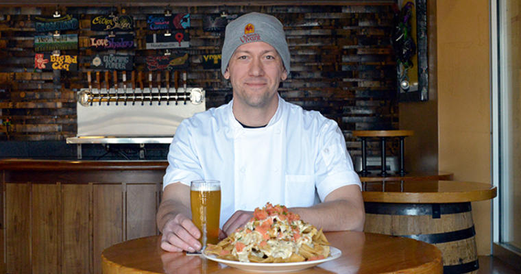 Chef Chris VanderMeer sits at a table with a plate of Duck Confit Nachos