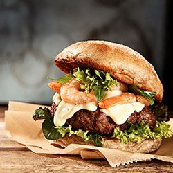 Gourmet burger with cheese, onions, lettuce and more.