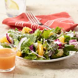 Salad topped with fruit and a side of vinaigrette dressing